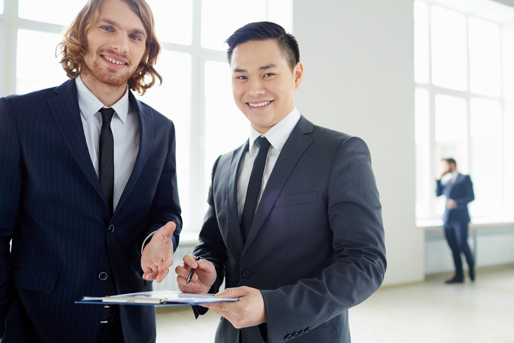 Young Businessmen Looking At Camera While Discussing Plan At Meeting In Office