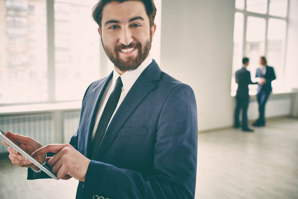 Portrait Of A Young Cheerful Businessman With A Tablet Looking At Camera On The Foreground