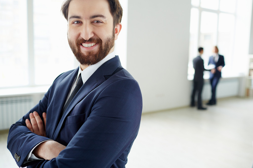Successful Businessman Looking At Camera With Two Colleagues Communicating On Background