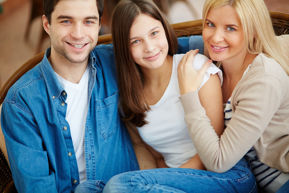 Portrait Of Happy Family Of Three Looking At Camera With Smiles