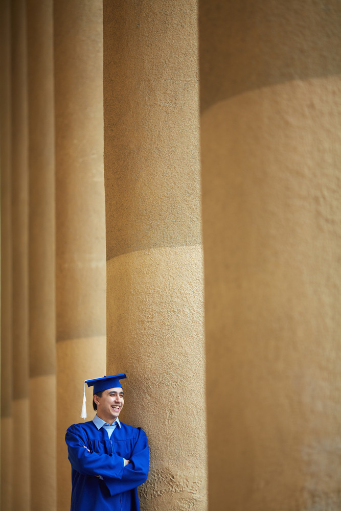 Portrait Of Happy Graduation Student Laughing By University Wall