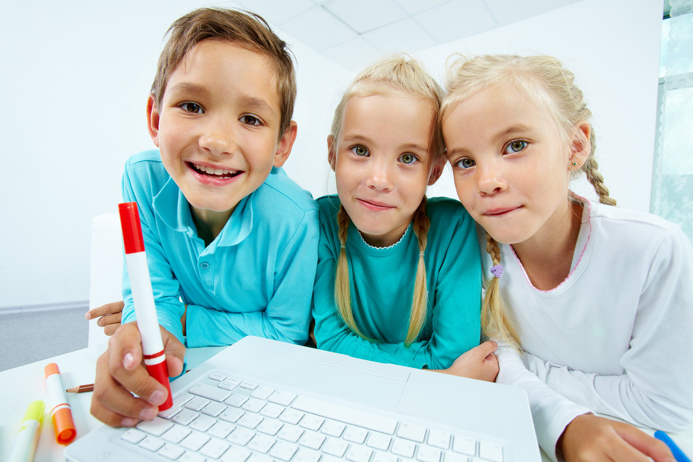 Smart Schoolchildren With Laptop Looking At Camera