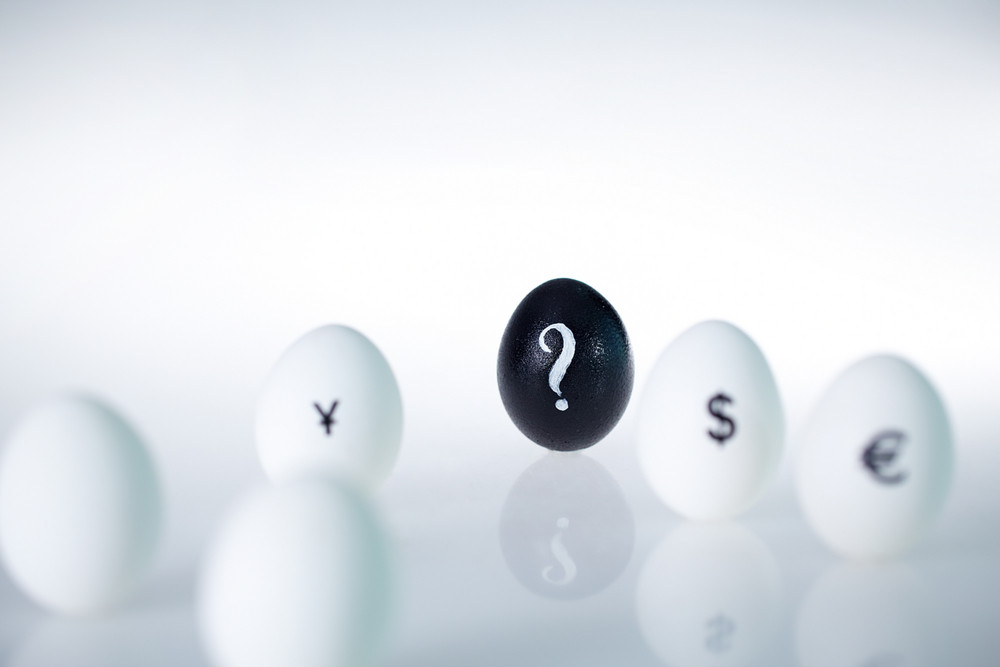 Close-up Of Black Egg With Question Mark On It Among White Eggs