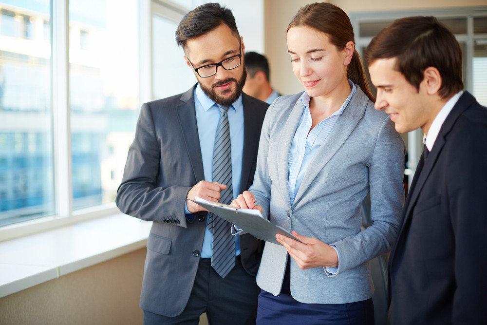 Confident Businesswoman With Clipboard Consulting Her Partners In Office