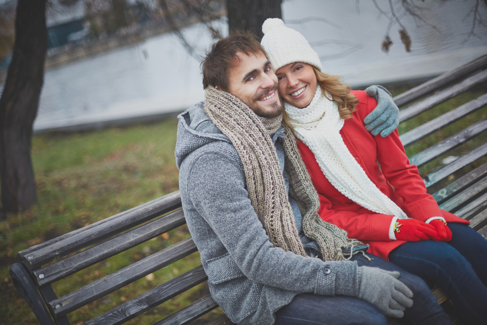 Image Of Affectionate Couple Sitting On The Bench And Looking At Camera In Park