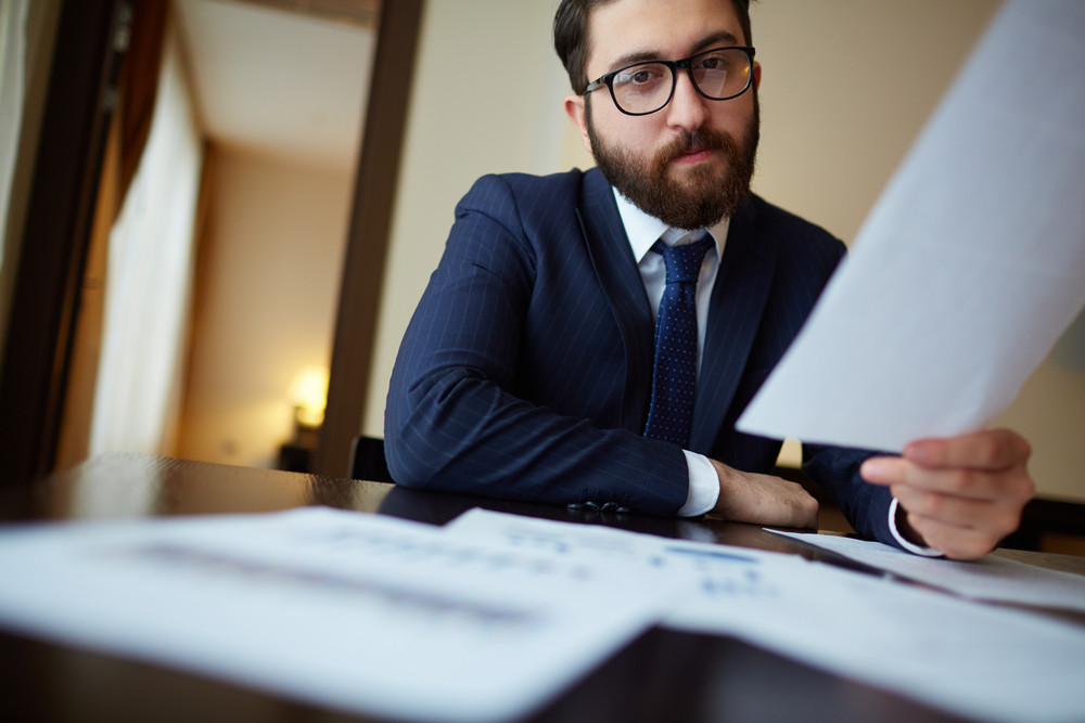 Serious Businessman With Document Looking At Camera In Office