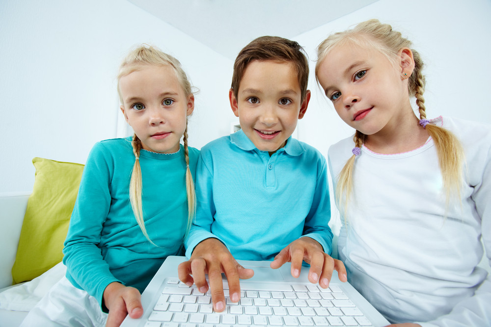 Smart Schoolboy Typing Between Twin Girls
