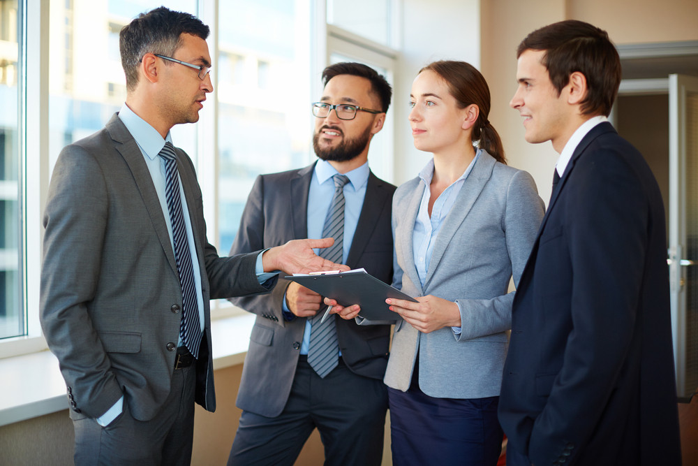 Confident Businessman Explaining His Idea To Female And Male Partners In Office