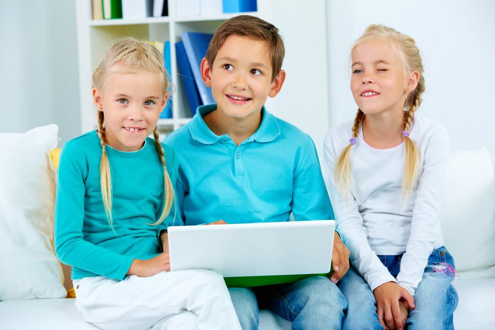 Smart Schoolchildren With Laptop Sitting On Sofa