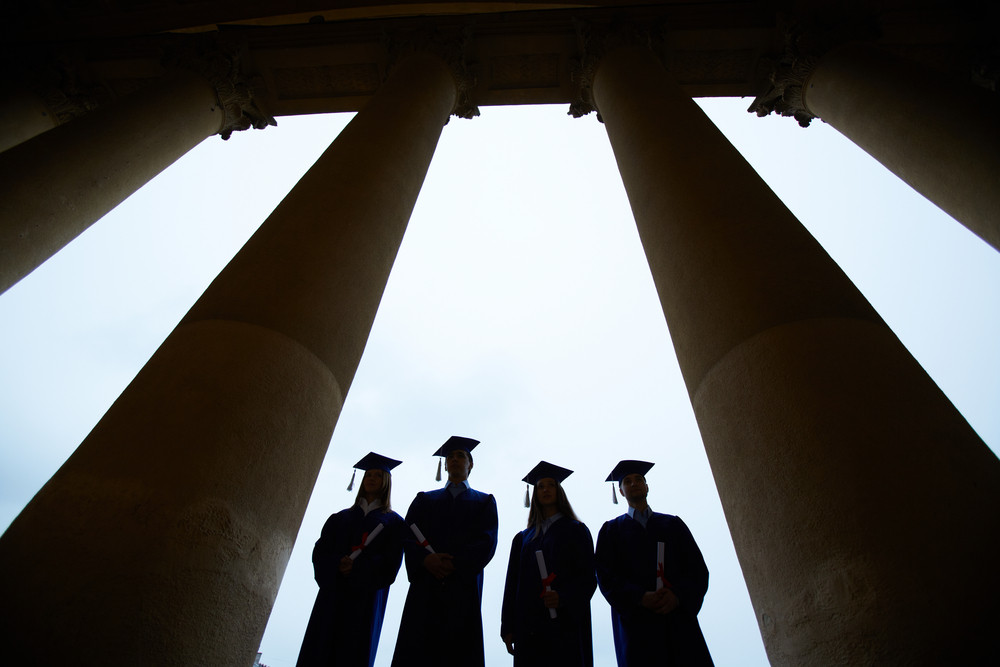 Outlines Of Four Graduates Between Columns Of University Building