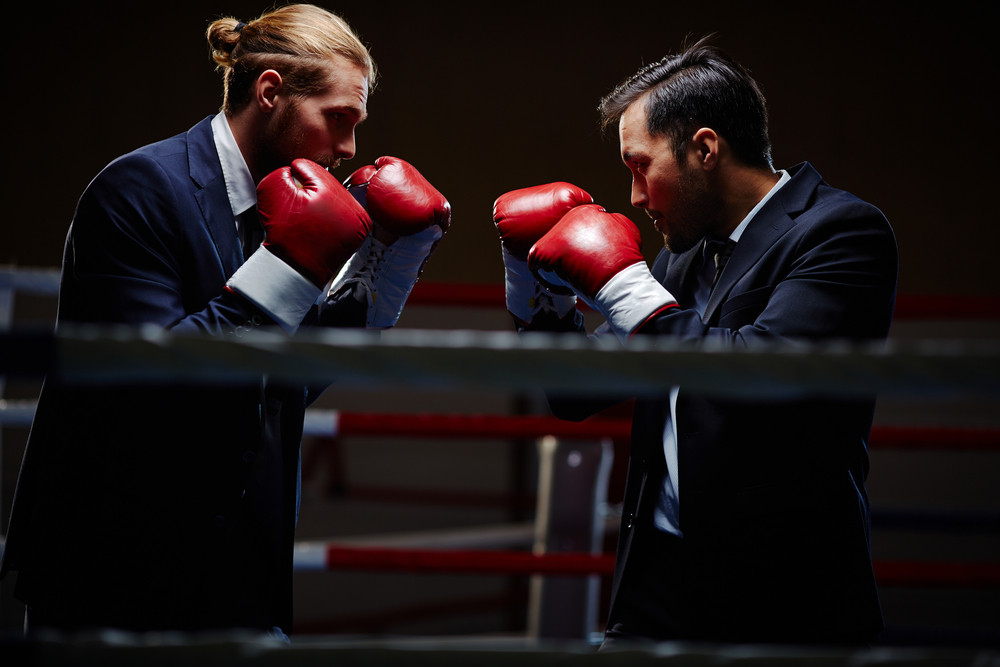 Business Boxers Attacking One Another