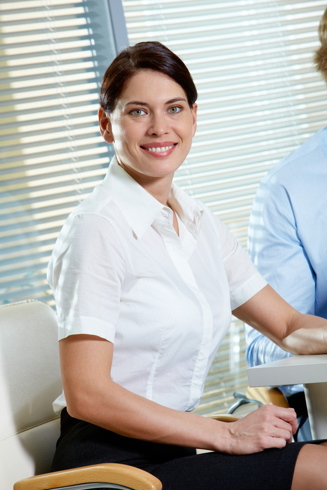 Portrait Of Pretty Woman Looking At Camera In Office