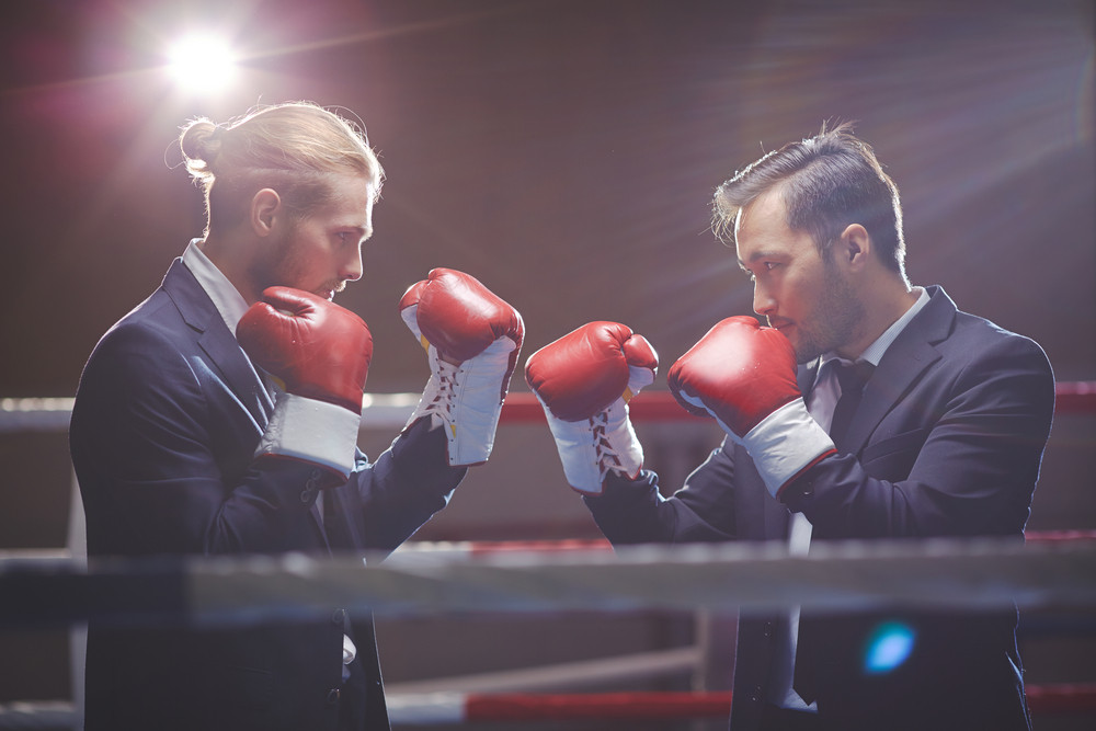 Businessmen In Suits And Boxing Gloves Attacking One Another
