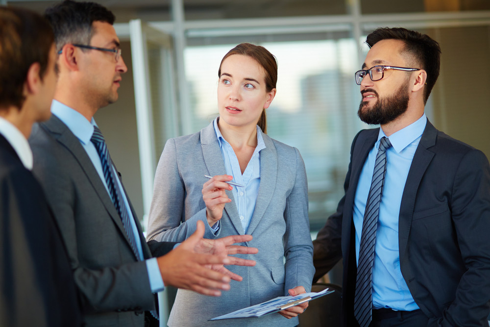 Elegant Business Partners Looking At Colleague At Meeting