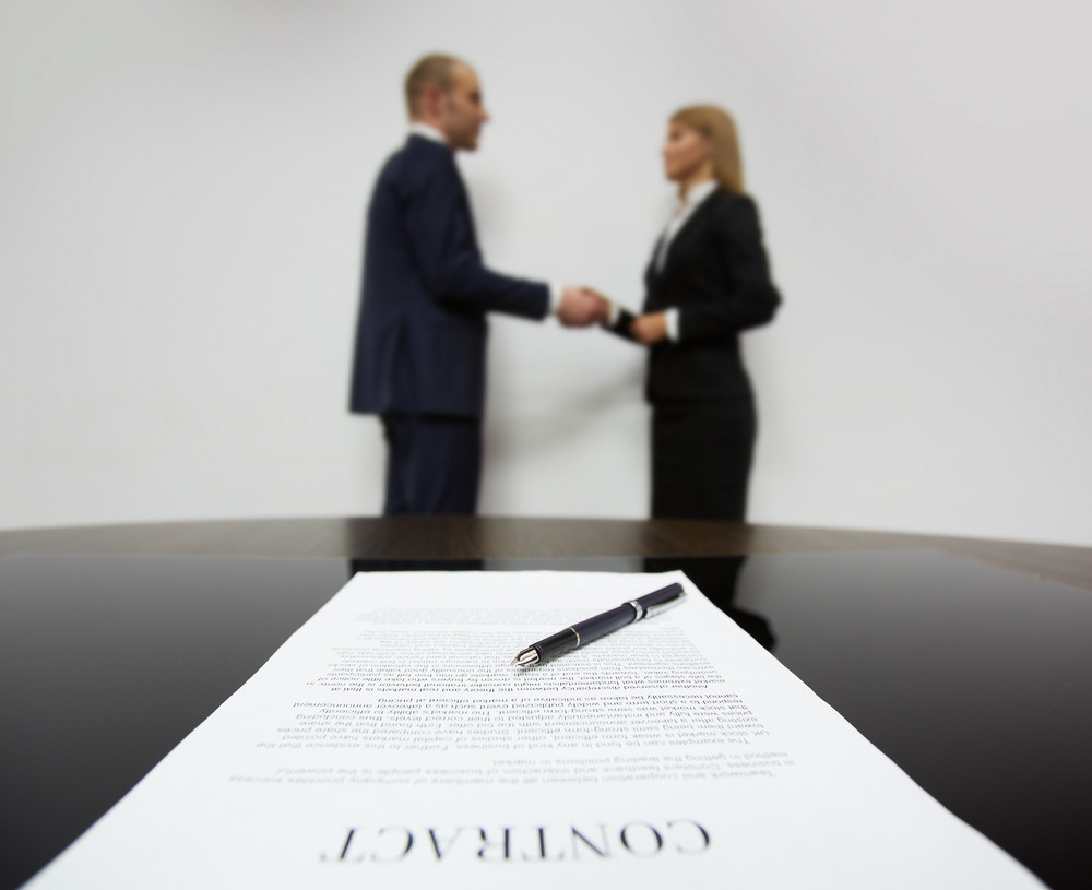 Image Of Business Contract On Background Of Business Partners Handshaking