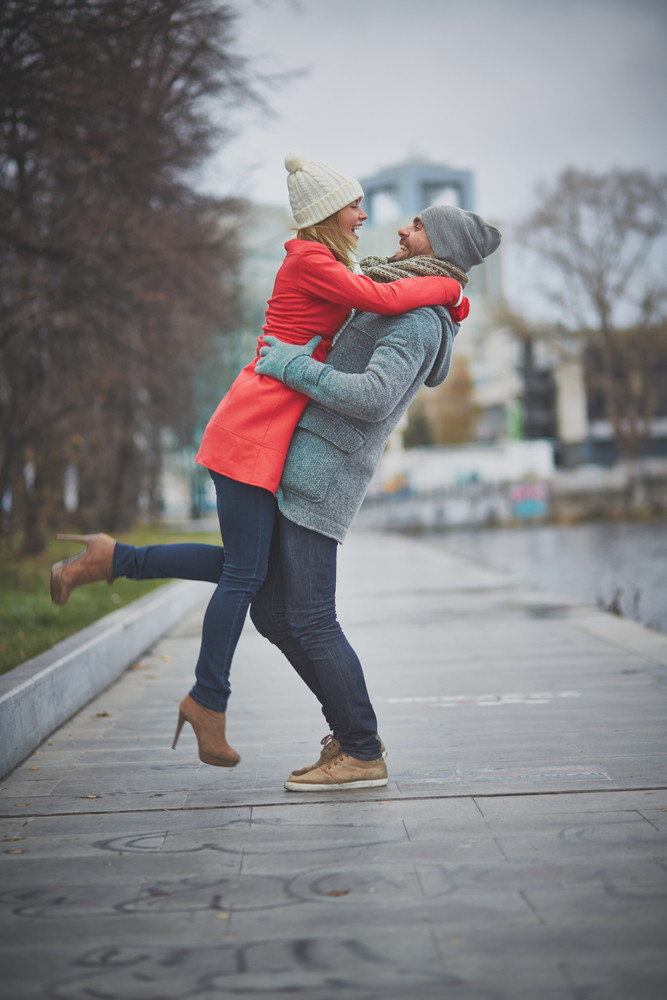 Portrait Of Happy Guy Holding His Girlfriend In Park