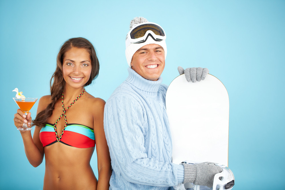 Portrait Of Cute Girl In Bikini Holding Cocktail And Handsome Man In Pullover Holding Snowboard