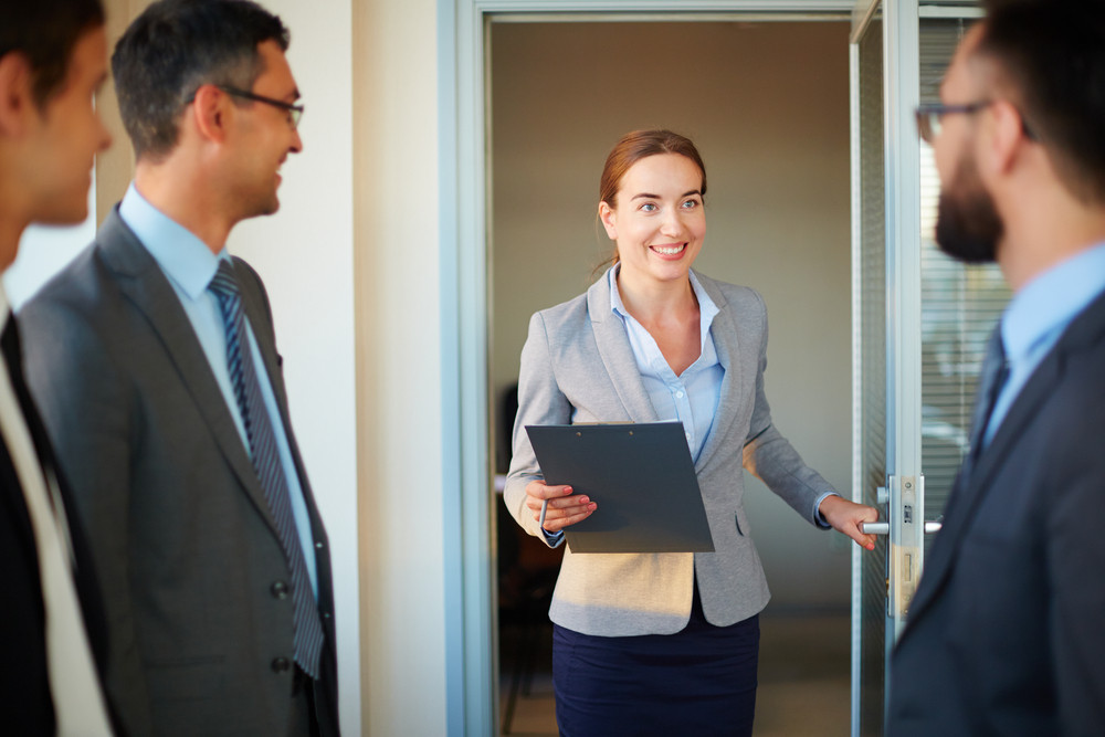 Happy Businesswoman With Clipboard Entering Office