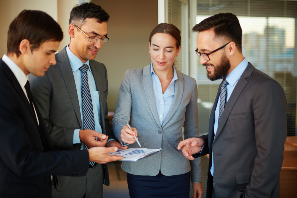 Confident Businesswoman Pointing At Document While Explaining Data To Her Partners In Office