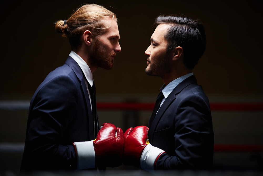 Two Male Business Boxers Looking At One Another In Isolation