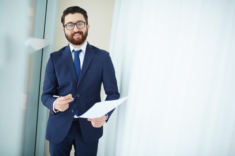 Portrait Of Elegant Businessman In Suit And Eyeglasses Looking At Camera