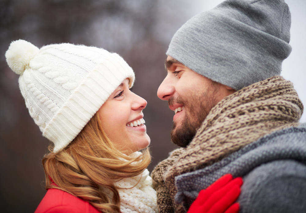 Portrait Of Happy Guy And His Girlfriend In Warm Clothes Looking At One Another