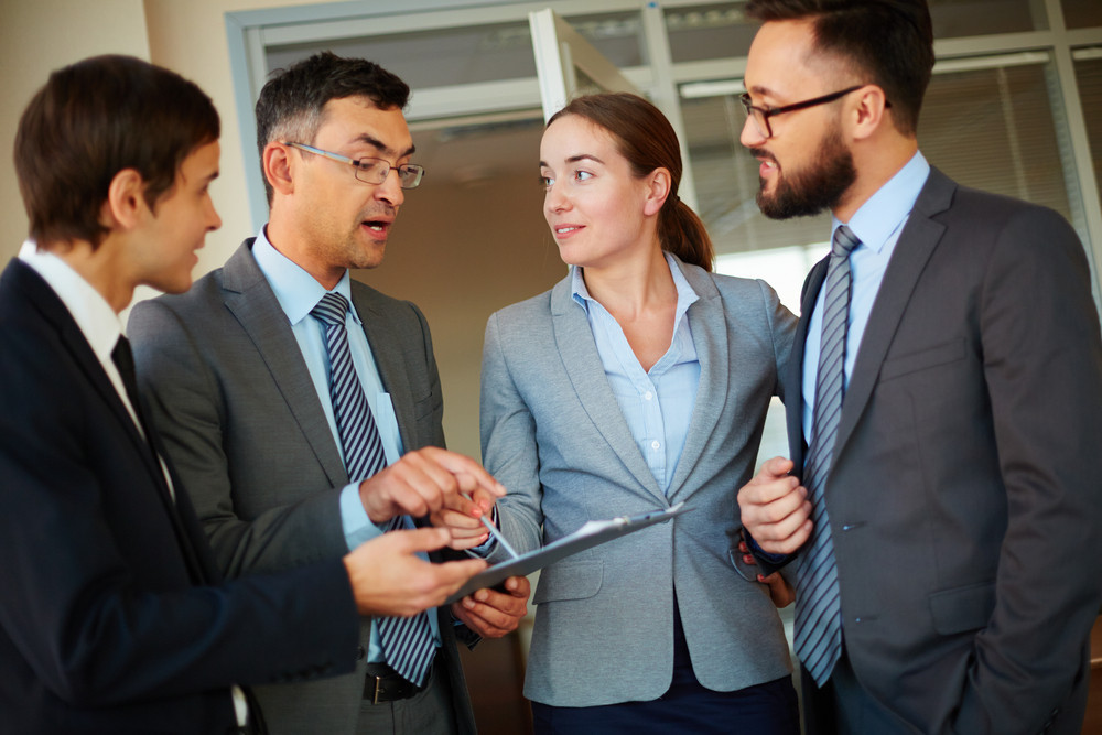 Smiling Businesswoman Pointing At Document And Looking At One Of Colleagues Explaining His Idea To Employees