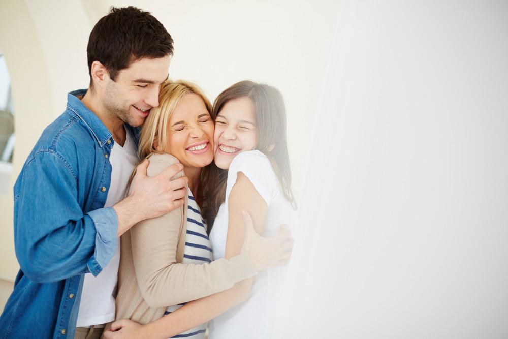 Portrait Of Joyful Family Of Three In Embrace