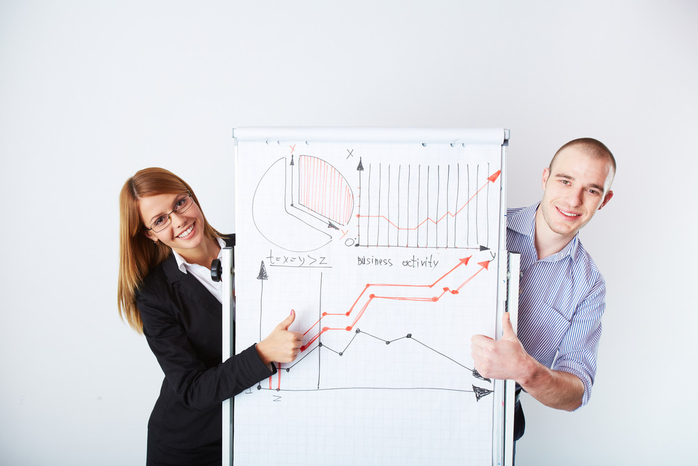 Successful Business Partners Standing By Whiteboard With Graph Of Market Analysis On It