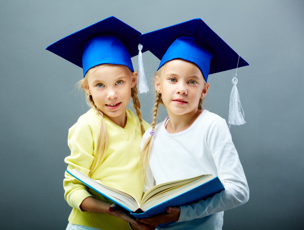 Portrait Of Lovely Twin Girls In Hats With Tassels Holding Open Book