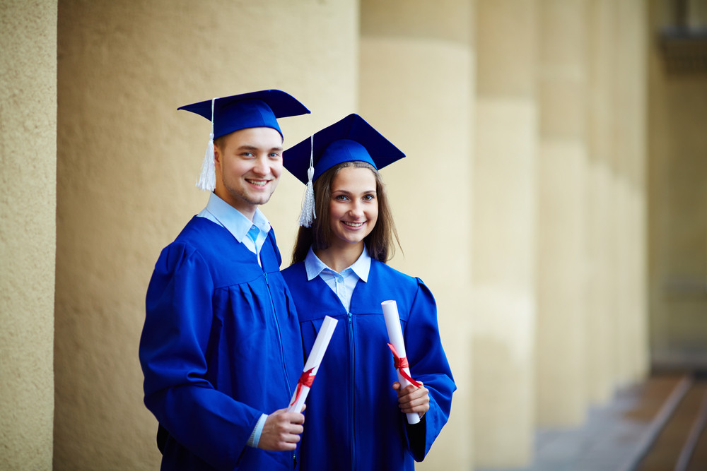 Two Happy Students In Graduation Gowns Looking At Camera