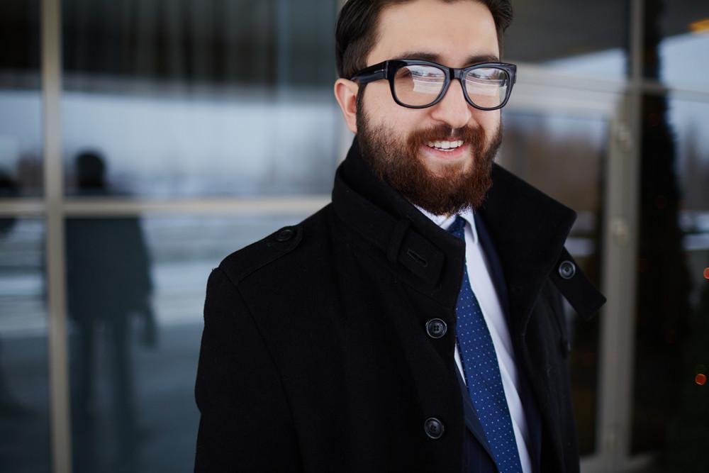 Portrait Of Elegant Businessman In Coat And Eyeglasses Looking At Camera Outside
