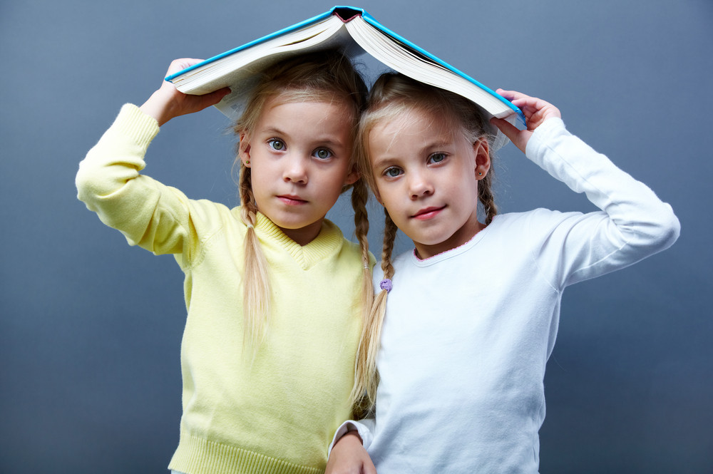 Portrait Of Lovely Twin Girls Holding Open Book Over Heads