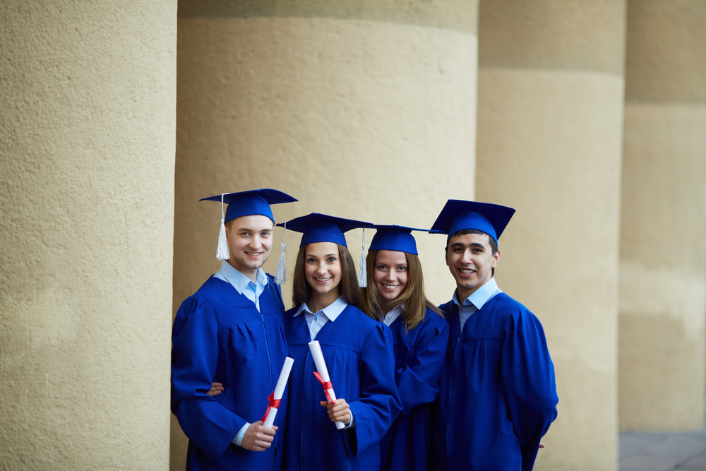 Group Of Smart Students In Graduation Gowns Holding Diplomas And Looking At Camera