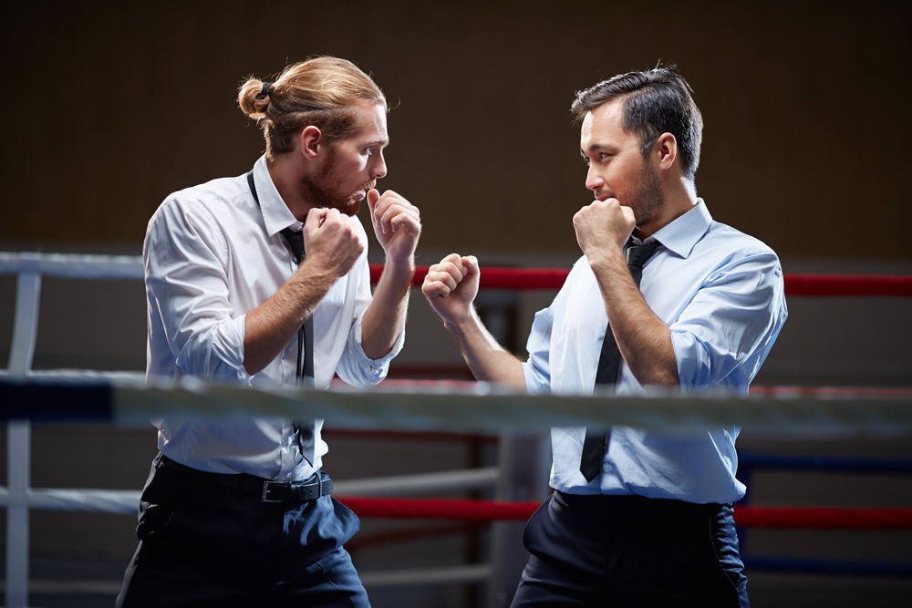 Businessmen Fighting With One Another On Boxing Ring