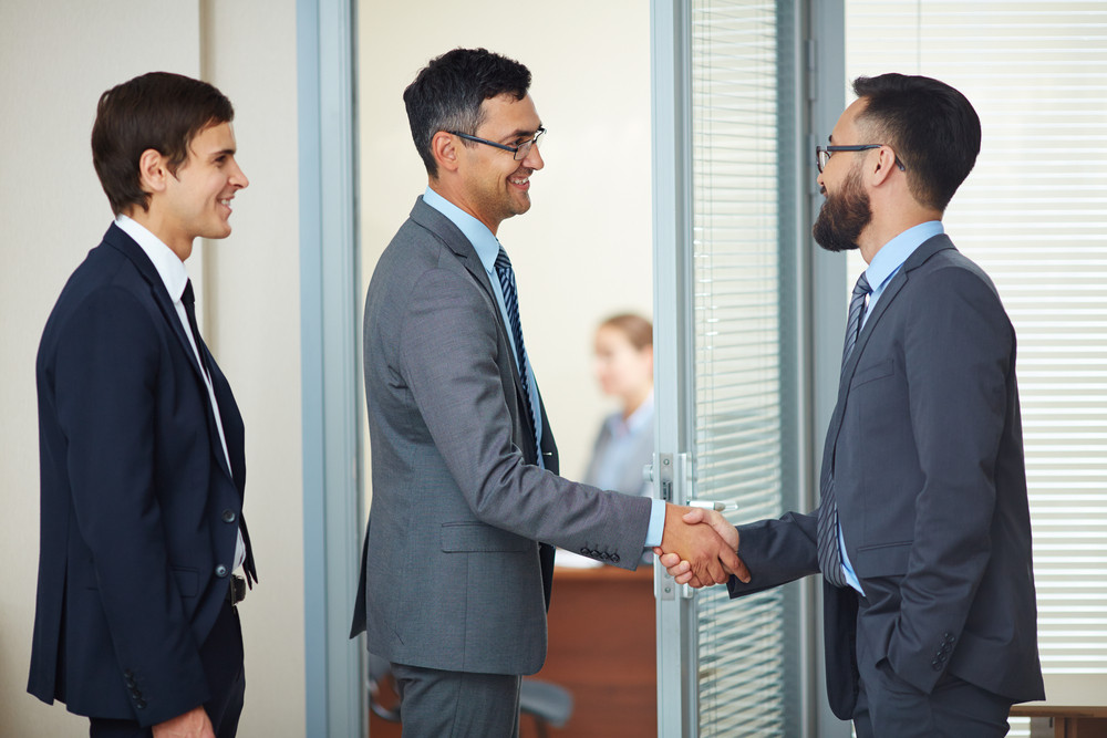 Two Businessmen Handshaking In Office After Signing Contract