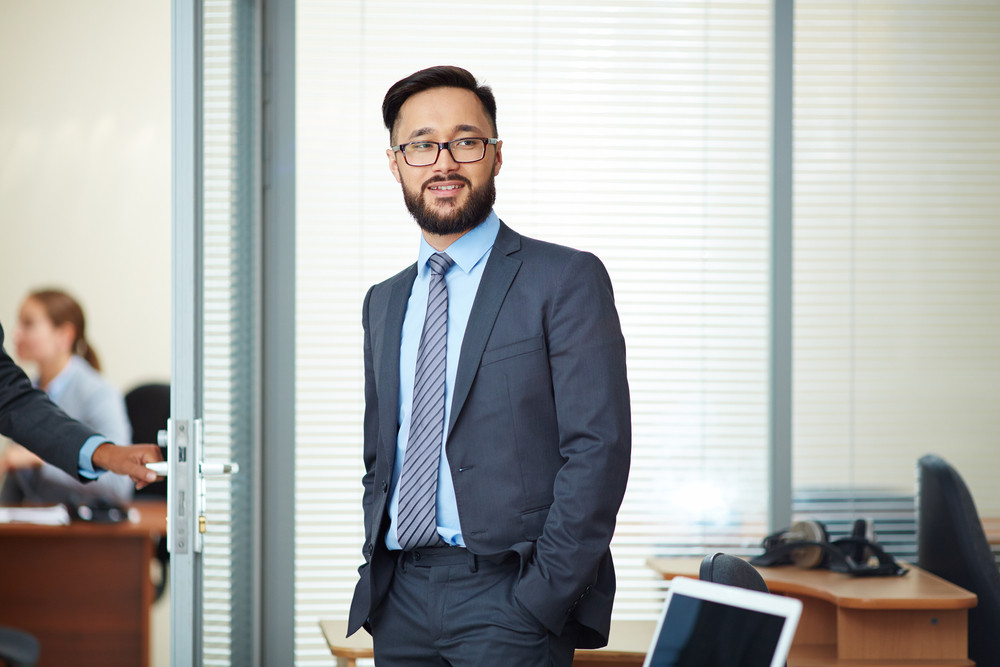 Happy Businessman In Eyeglasses And Suit Standing In Office