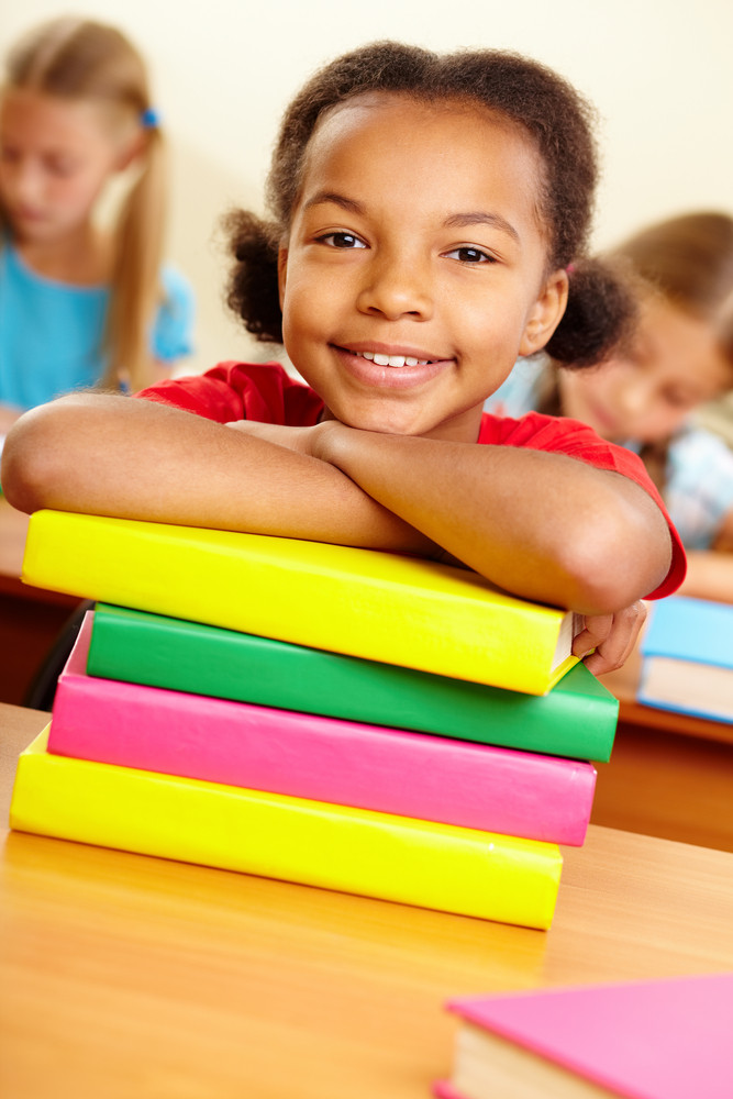 Portrait Of Lovely Girl With Stack Of Books Looking At Camera At Workplace