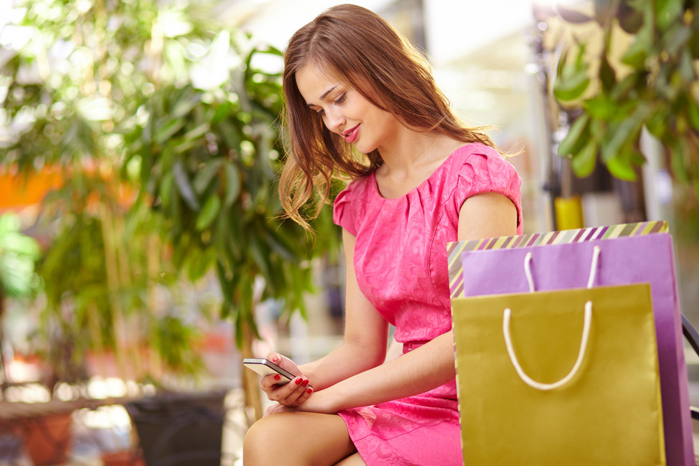 Adorable Girl With Cellphone Sitting In The Mall With Shopping Bags Near By