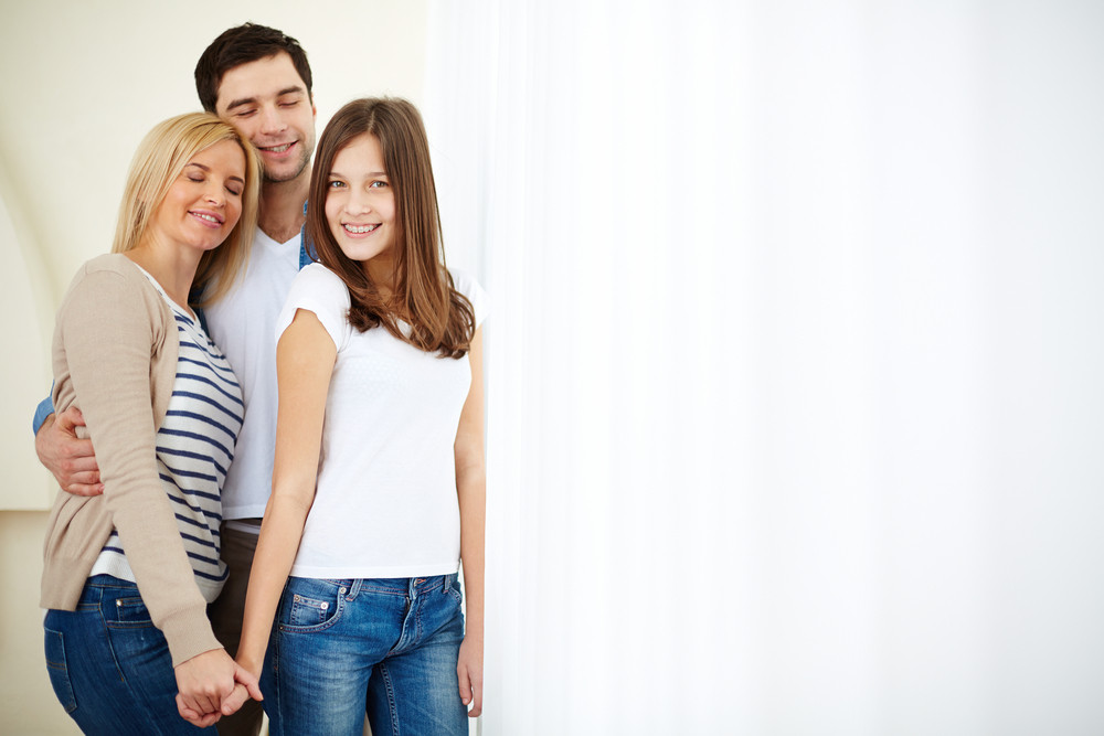 Portrait Of Affectionate Family Of Three In Isolation