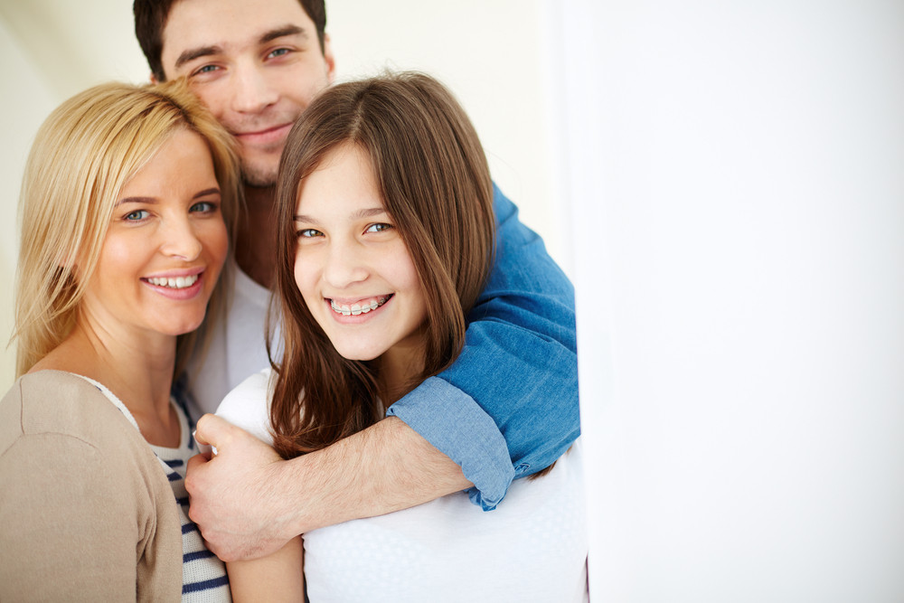 Portrait Of Affectionate Family Of Three Looking At Camera With Smiles In Isolation