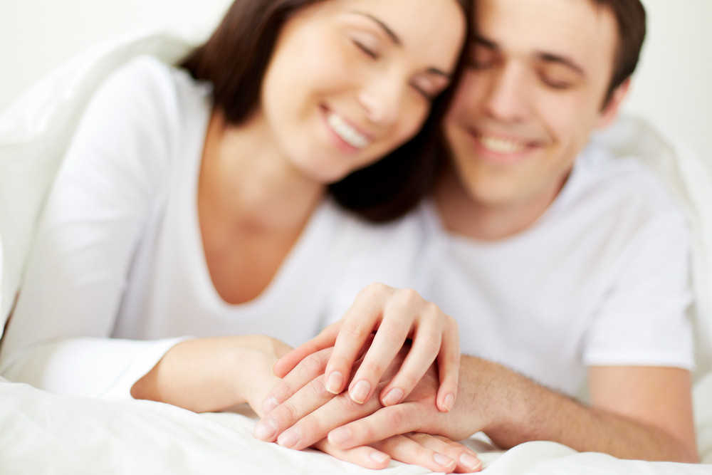 Hands Of Amorous Young Couple In Bed