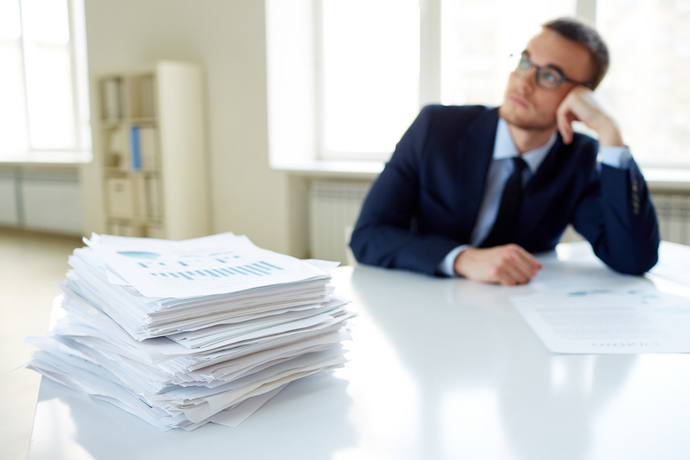 Stack Of Documents On The Desk And Pensive Male Employee Working On Background