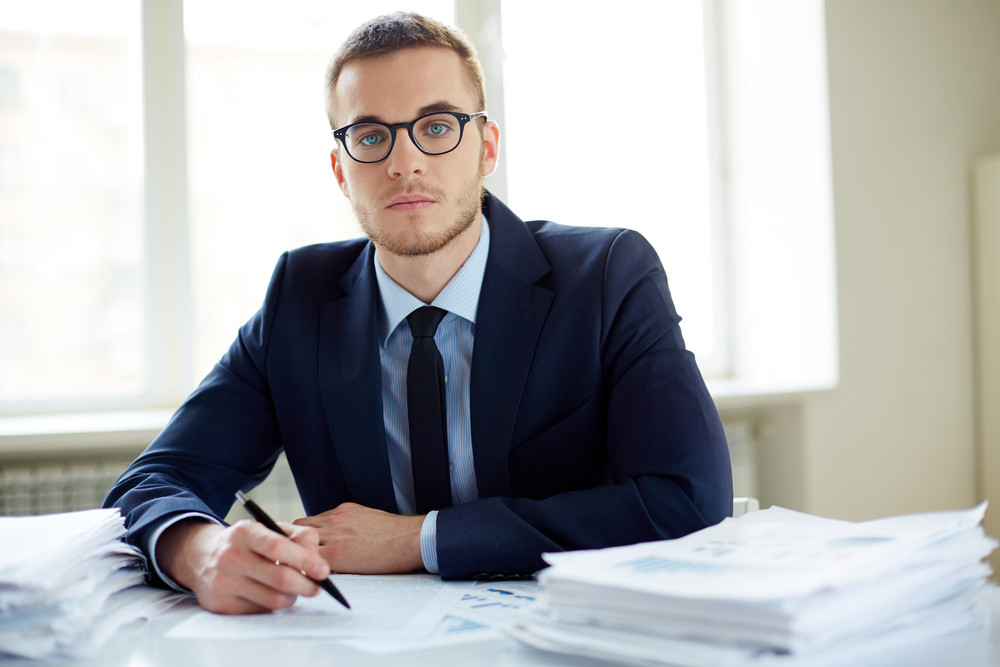Portrait Of An Office Worker Sitting At Workplace And Looking At Camera