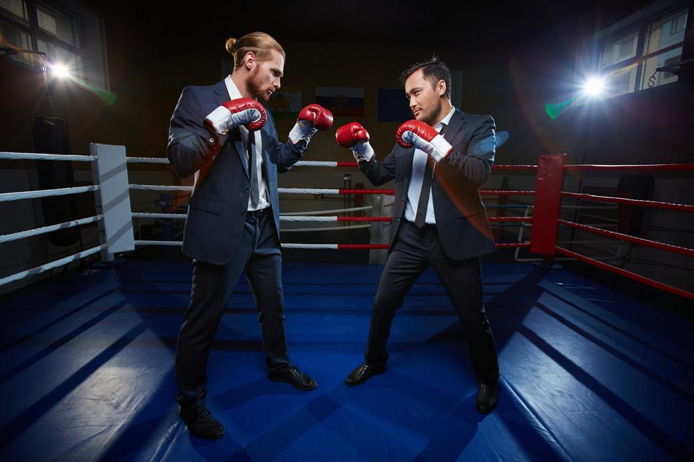 Professional Businessmen In Suits And Boxing Gloves Standing Opposite One Another On Boxing Ring
