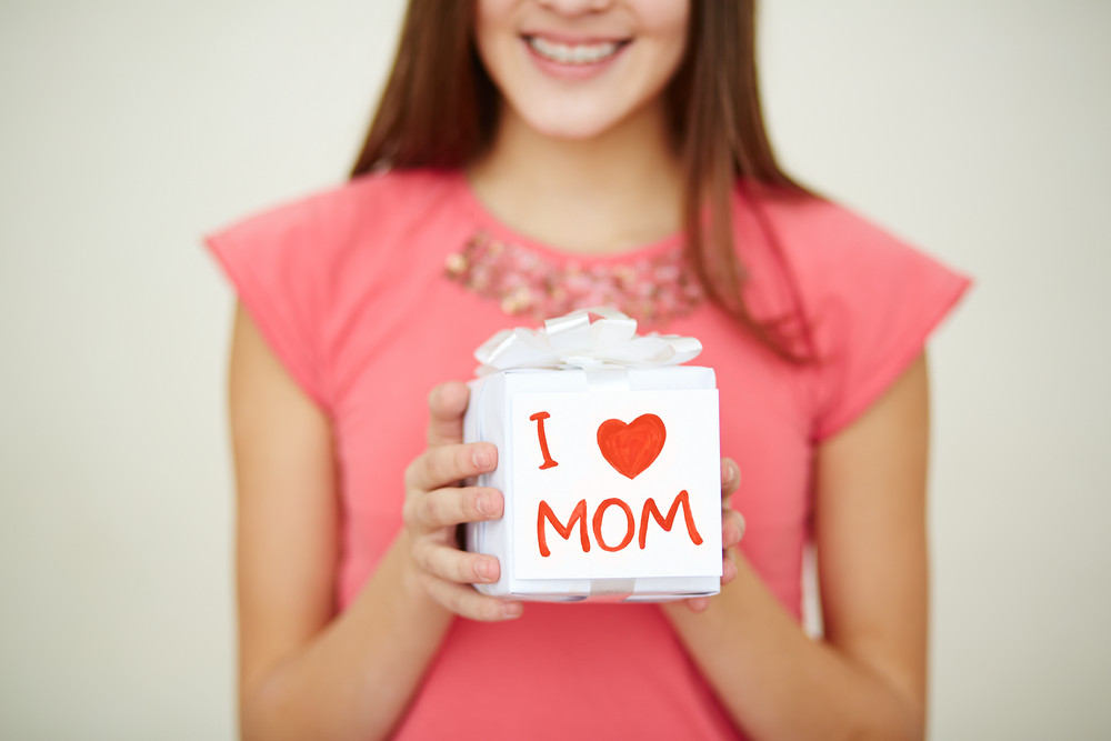 Close-up Of Teenage Girl Holding Giftbox For Mom