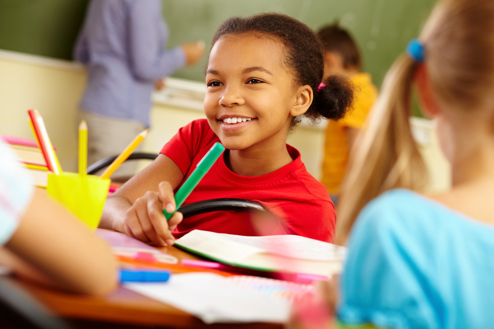 Portrait Of Cute Girl Holding Crayon While Looking At Classmate At Lesson