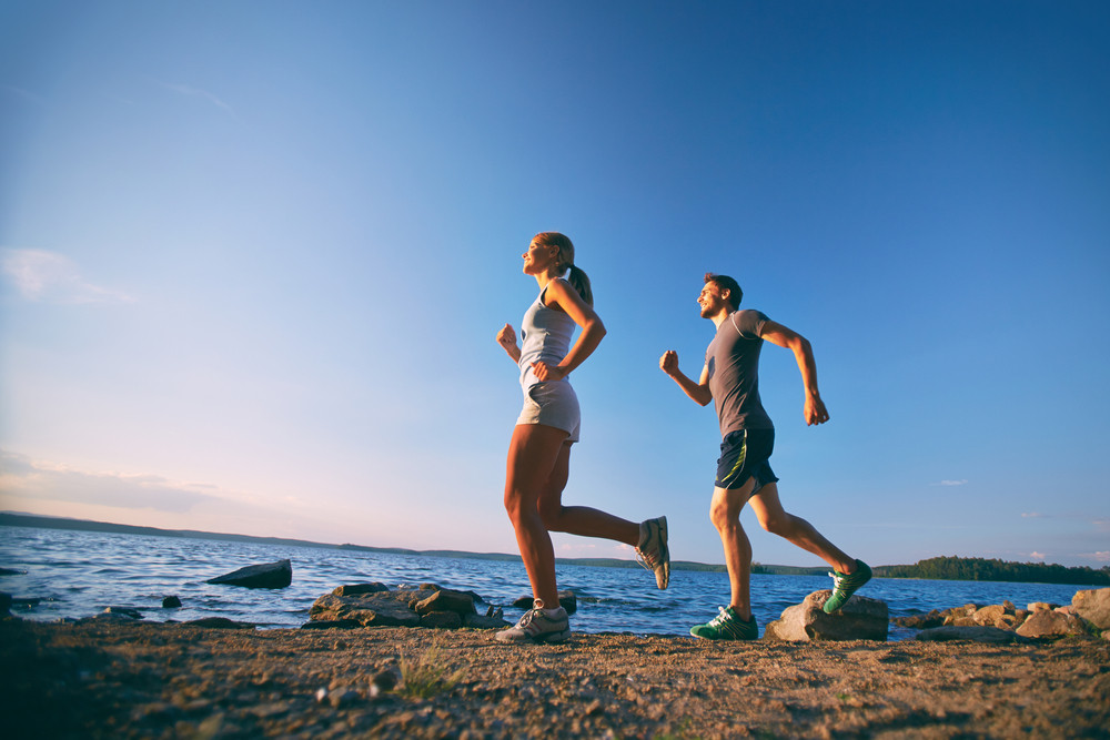 Photo Of Young Couple Running On The Coastline