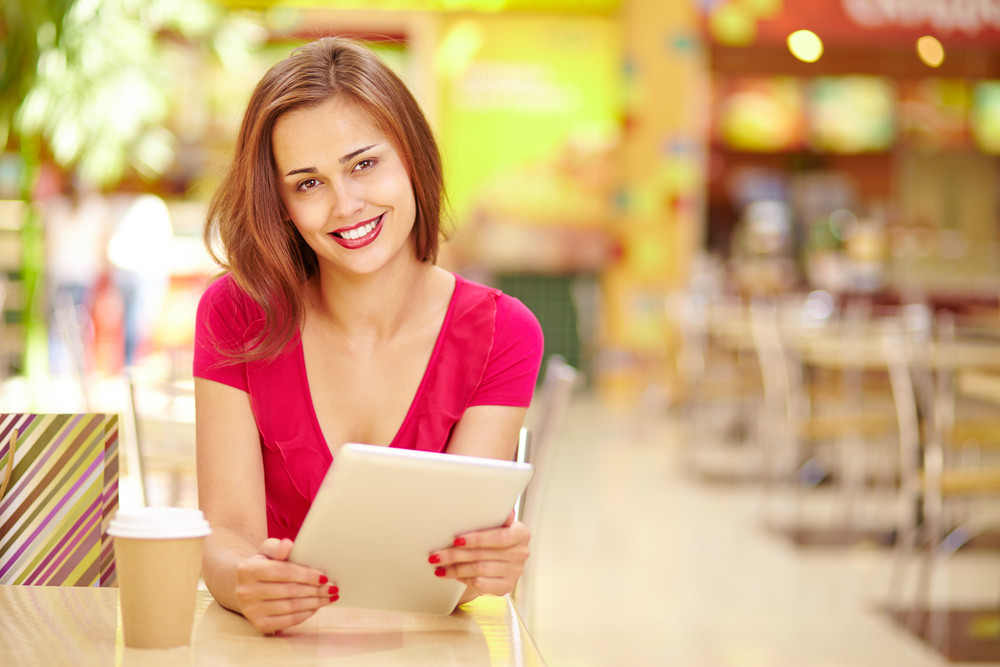 Smiling Girl Holding A Digital Pad While Sitting At The Table In A Summer Cafe