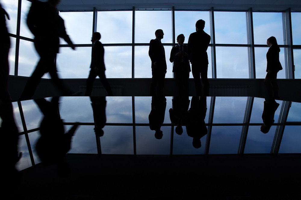Three White Collar Workers Communicating In Office Against Window With Several Business Partners Walking Around